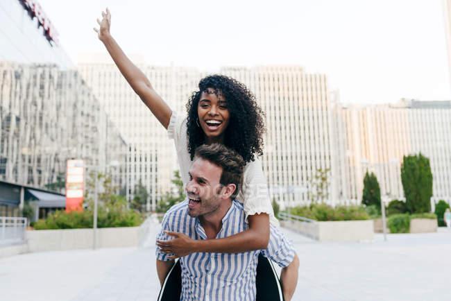 Homme donnant piggyback tour à afro-américaine femme tout en s'amusant sur la rue de la ville ensemble — Photo de stock
