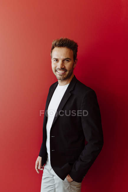 Portrait of smiling man in elegant outfit standing on bright red background — Stock Photo