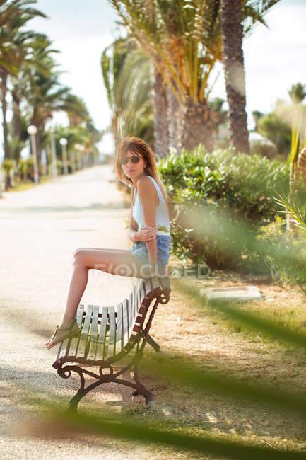 Slim жінка в купальник і джинсового шорти, сидячи на лавці в парку тропічний курорт і, дивлячись на камеру — стокове фото