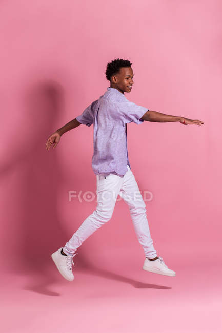 Smiling young black man in white denim and shirt jumping against pink background — Stock Photo