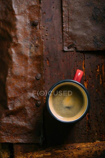 Copa de esmalte de café en la superficie de madera rústica - foto de stock