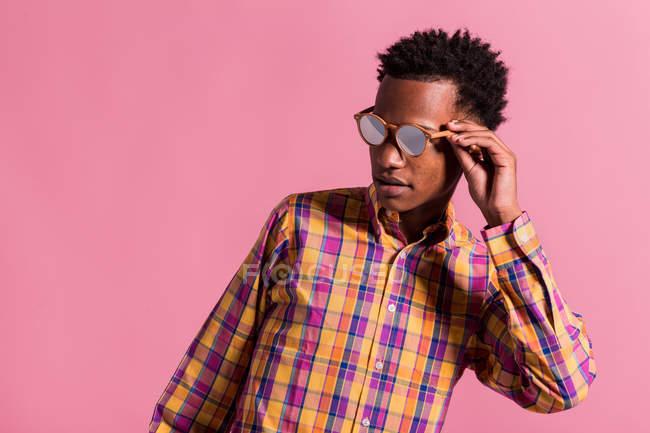 Hombre hipster estilo en gafas de sol y camiseta en fondo rosa - foto de stock