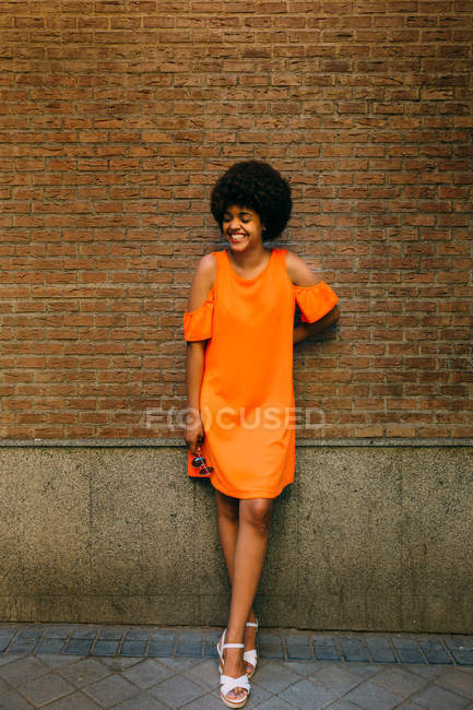 Attractive African American woman in stylish sunglasses smiling while standing near brick wall — Stock Photo