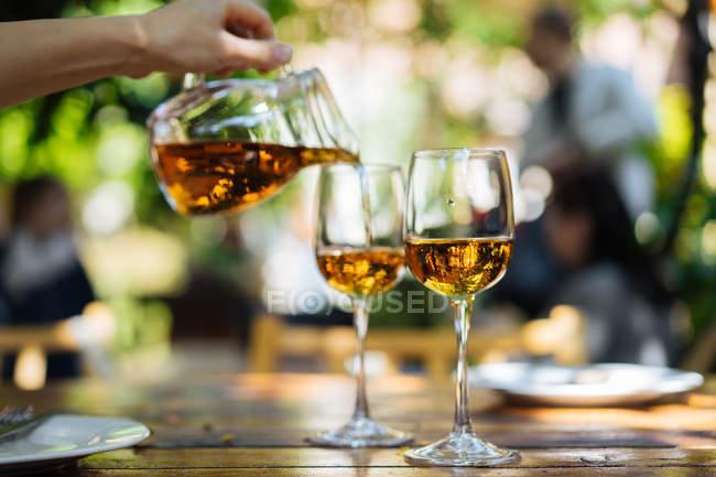 Menschliche Hand gießt Weißwein aus Glaskanne in Gläser auf Tisch im Freien — Stockfoto