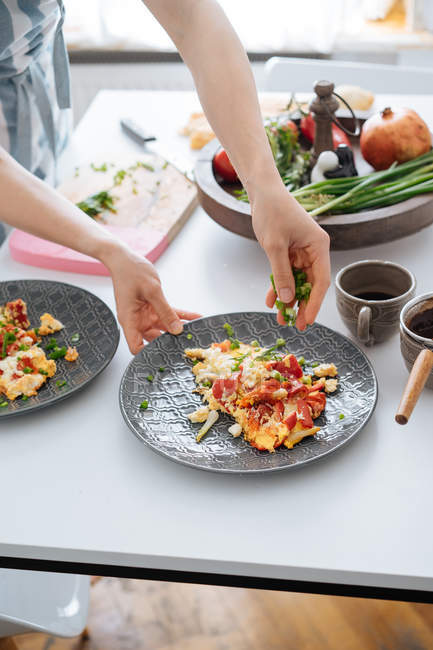 Human hands sprinkling with onion omelette with vegetables on plate — Stock Photo