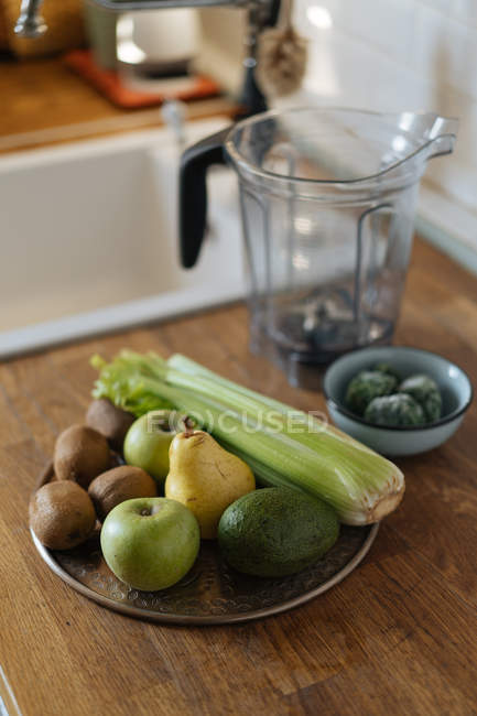 Fresh green vegetables and fruits on plate on wooden counter in kitchen — Stock Photo