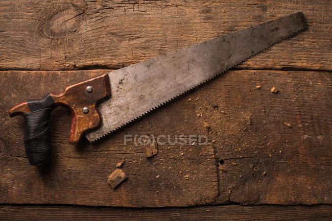 Sega a mano arrugginito su superficie di legno del carpentiere — Foto stock