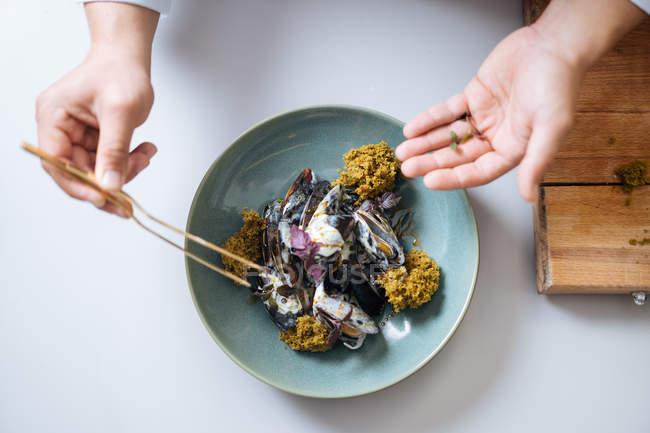 Человека руки гарнировать блюдо северных из морепродуктов с мидиями и сливочным соусом на плите — стоковое фото