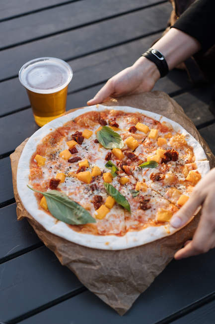 Close-up of female hands holding takeaway pizza next to glass of beer — Stock Photo