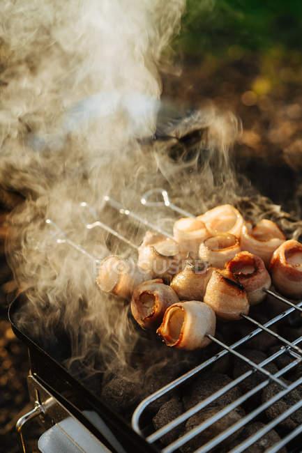 Primo piano della piastra portatile con bruciando carbone di legna e spiedini con pancetta strisce grigliare — Foto stock