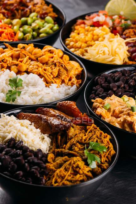 Bols en céramique noire de nourriture assortie de la cuisine asiatique — Photo de stock