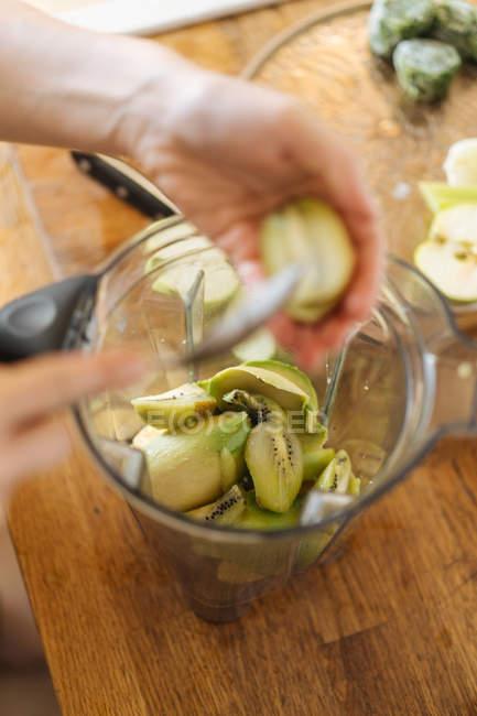 Manos humanas pelar la mitad con una cuchara y la mezcla con frutas en la licuadora la taza de batido verde kiwi - foto de stock