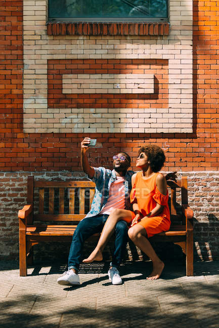 Black man and barefoot woman kissing air and taking selfie while sitting on bench near brick wall — Stock Photo