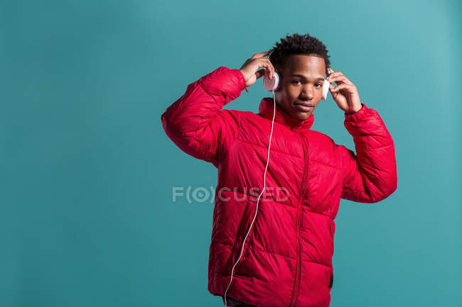 Trendy man in red puffy jacket and headphones on blue background — Stock Photo