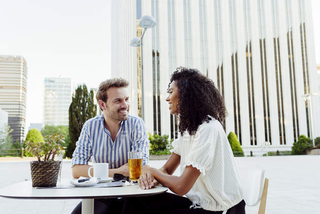 Smiling multiracial couple looking at each other while spending time in outdoor cafe together — Stock Photo
