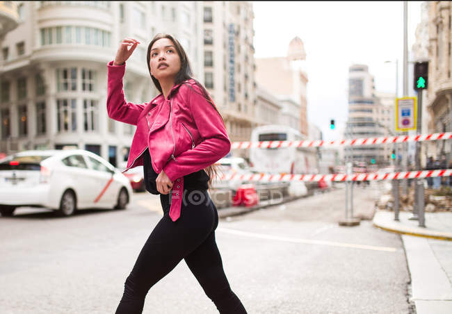 Slim woman in pink leather jacket crossing street and looking away — Stock Photo