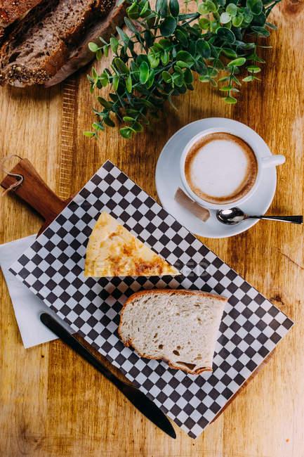 Kaffee in weißem Porzellantasse auf Untertasse mit karierten Schneidebrett mit Scheibe Brot und Gebäck — Stockfoto