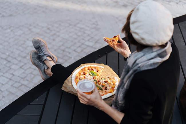 Женщина сидит на подиуме на улице со стаканом пива и пиццей на вынос — стоковое фото