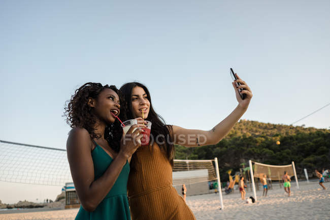 Young women taking selfie with drinks on sandy town beach — Stock Photo