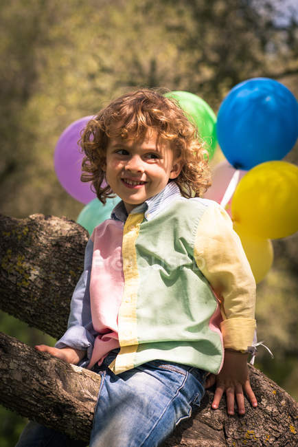 Smiling preschooler sitting on tree with colorful balloons — Stock Photo