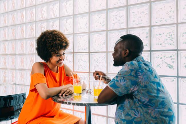 Seitenansicht des Paares lächelnd und sahen einander am Café-Tisch sitzen und mit Getränken — Stockfoto