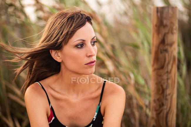 Young woman looking away in field grass — Stock Photo