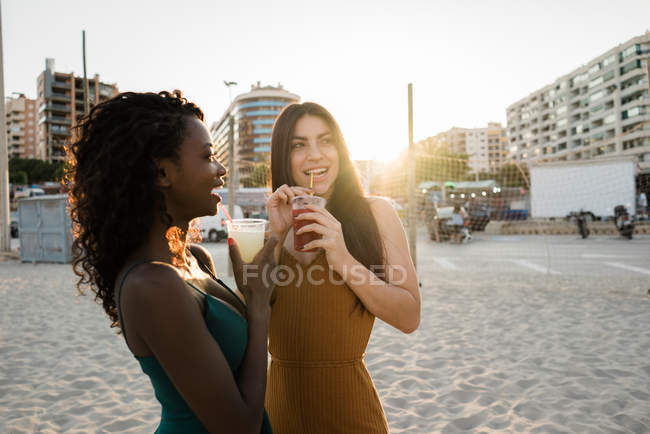 Young women enjoying drinks in soft light at city coastline — Stock Photo