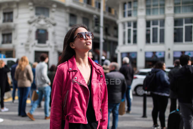 Trendy modern young woman wearing pink leather jacket with sunglasses standing on street in sunlight — Stock Photo