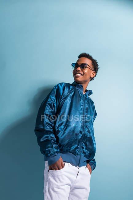 Sonriente hombre negro en chaqueta azul bombardero de pie sobre fondo azul - foto de stock