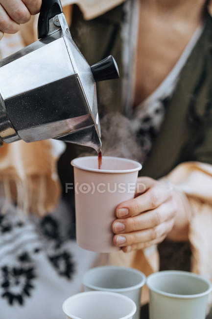 Female hands pouring freshly brewed coffee from coffee maker into cups at picnic — Stock Photo