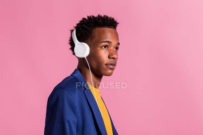 Thoughtful stylish man in jacket and headphones on pink background — Stock Photo