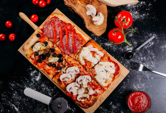 Cut pizza with cheese, sauce and sliced eggplants on wooden board on dark table — Stock Photo