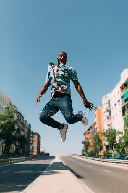 Handsome African American man in casual clothing jumping and shouting over road in city — Stock Photo