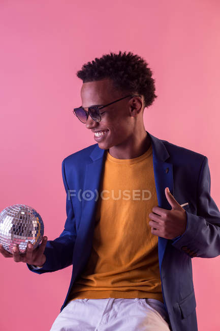 Trendy party man sitting with disco ball on pink background — Stock Photo