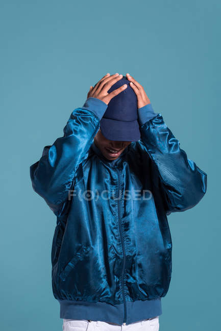 Trendy ethnic man wearing shiny blue bomber jacket and cap against blue background — Stock Photo