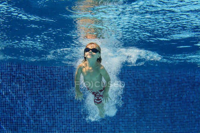 Elementary age boy in goggles swimming in blue pool underwater with air bubbles — Stock Photo