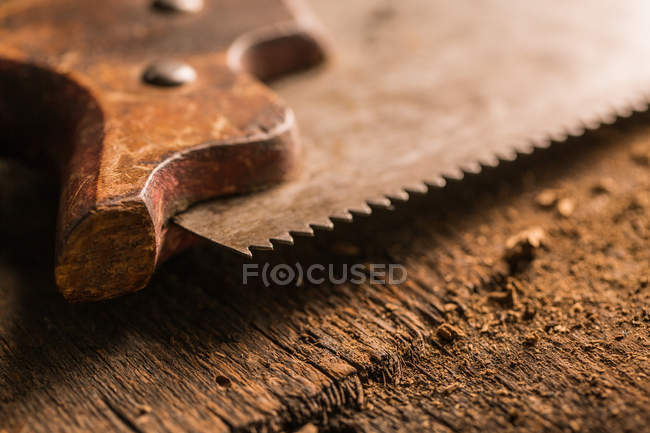 Close-up of old rusty handsaw on wooden surface — Stock Photo