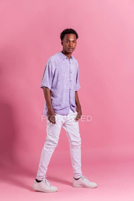 Stilvolle junger Mann in weißen Jeans und Shirt posiert auf rosa Hintergrund — Stockfoto