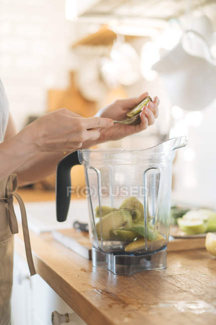 Mujer manos poner frutas en un tazón licuadora de batidos verdes - foto de stock