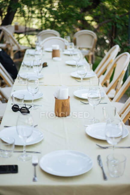 Beautiful table with light cloth and rattan chairs around set with empty wine glasses and plates outdoors on pavement with trees and grass around — стокове фото