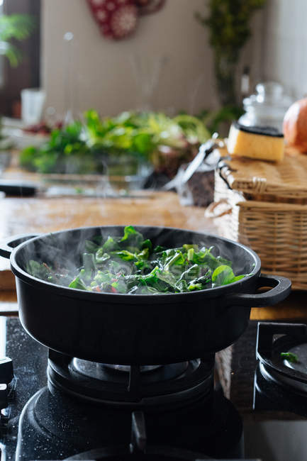 Cozinhar espinafre deixa em panela no fogão a gás — Fotografia de Stock