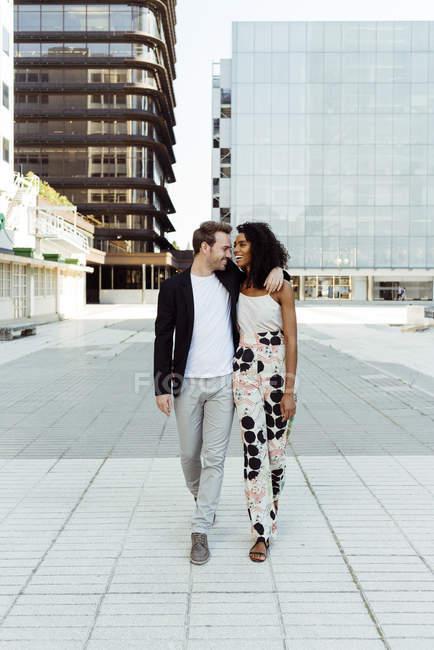 Веселая многорасовая пара обнимается во время прогулки по городской улице вместе — стоковое фото