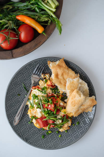 Fried omelette with chopped vegetables and bread on plate — Stock Photo
