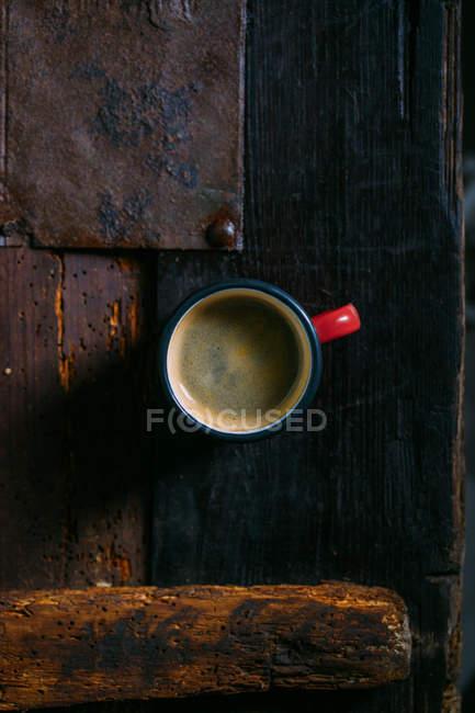 Чашка эмали кофе на деревенской деревянной поверхности — стоковое фото