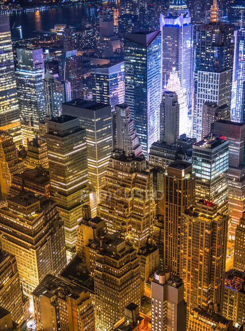 Magnificent aerial view of high modern glass and concrete buildings in metropolis illuminated by bright lights at night — Stock Photo