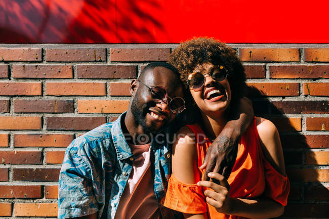 Attractive African American man and woman in stylish sunglasses laughing and hugging against brick wall on street — Stock Photo