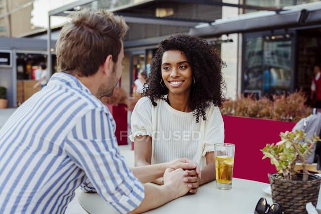 Romantisches gemischtrassige Paar Hand in Hand und sahen einander beim Sitzen am Tisch im Café im freien — Stockfoto
