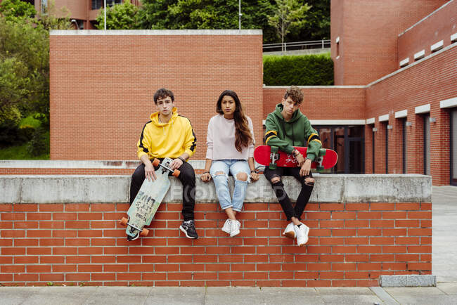 Teenagers with skateboards on fence — Stock Photo