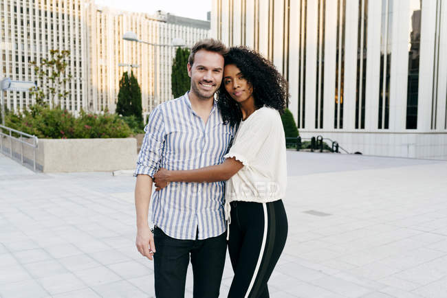 Romantic multiracial couple hugging on street together — Stock Photo