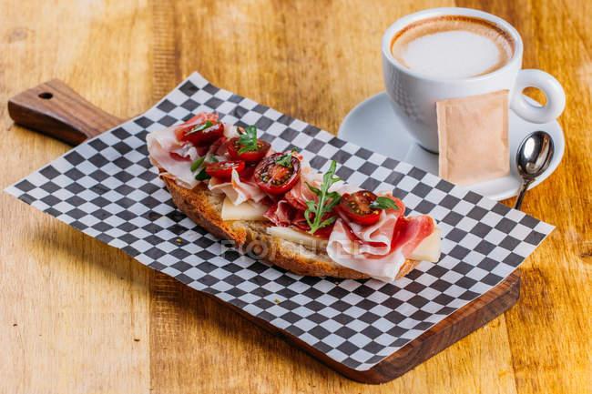 Бутерброд з беконом і помідорів чері на дерев'яний стіл з чашкою капучино — стокове фото